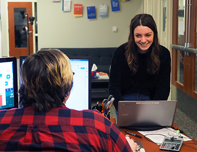 a young woman approaches a desk. Another young woman is facing her and has computer screens open