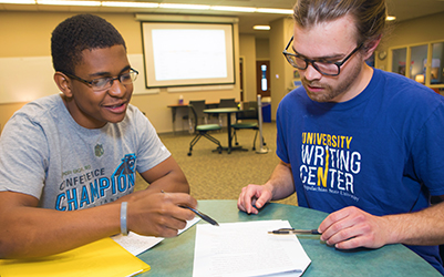 An African American student in a session with a white man wearing a UWC T-shirt