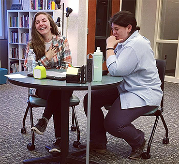 two young women at a round table, both laughing