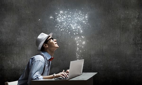young man typing on a laptop, glowing letters flow upward